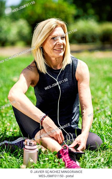 Mature woman resting in the grass of a park after exercising