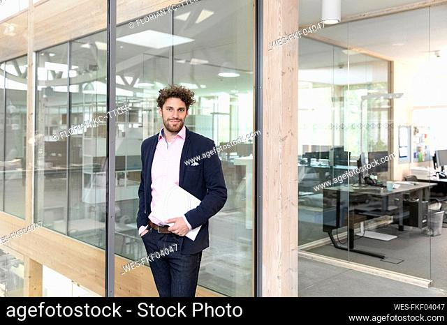 Male entrepreneur with document against glass wall at office