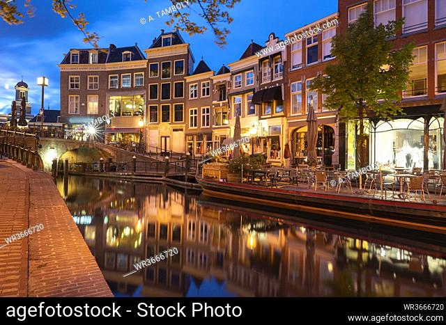 Netherlands, South Holland, Leiden, Sidewalk cafe and row of townhouses reflecting in Nieuwe Rijn canal at dusk
