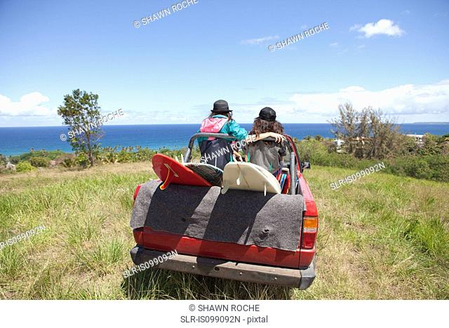 Off road vehicle driving toward beach with two women in back