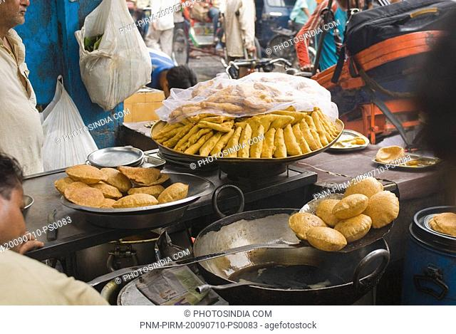 Man frying poori at a food stall, New Delhi, India