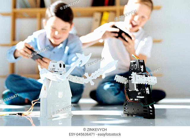 Excited players. Upbeat little boys sitting on the floor, holding game controllers and playing with their new black and white robots