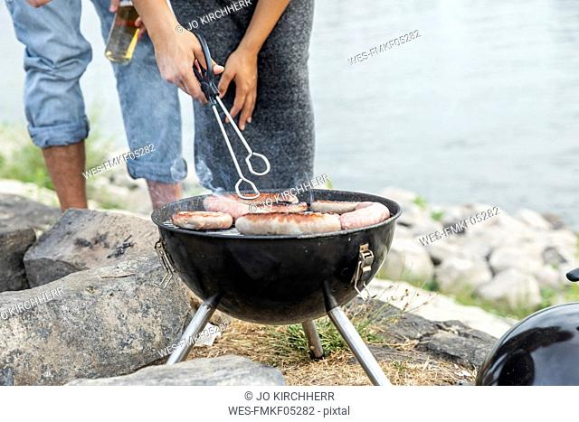 Close-up of couple having a barbecue at the riverside