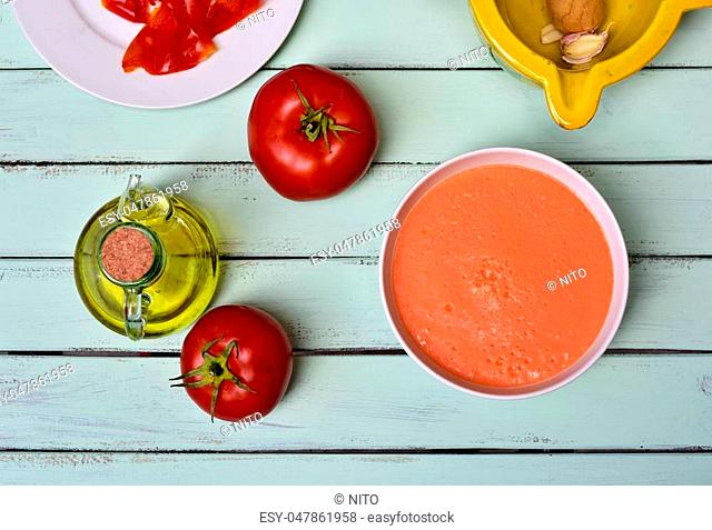 high-angle shot of a bowl with spanish gazpacho and some ingredient to prepare it, such as tomato, garlic and olive oil, on a blue rustic wooden table