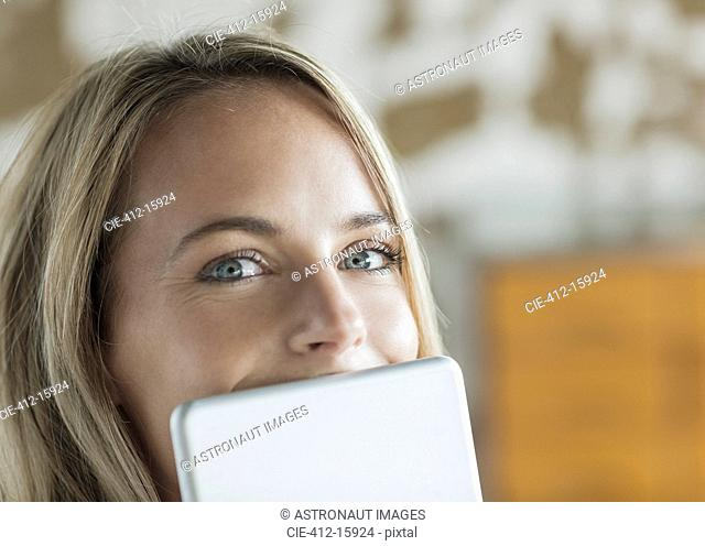 Close up portrait of woman behind digital tablet