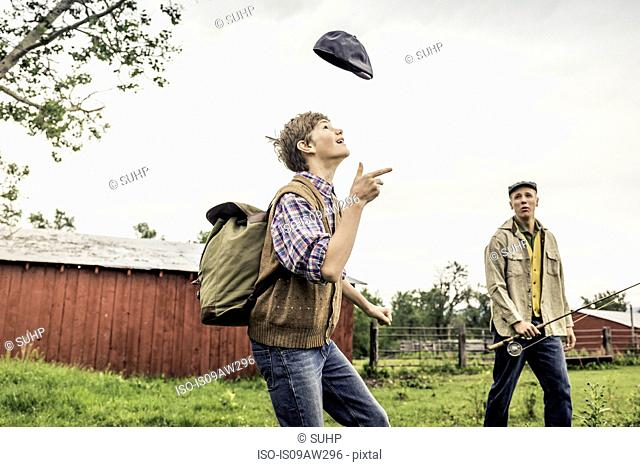 Man and boy on farm looking up throwing flat cap in air