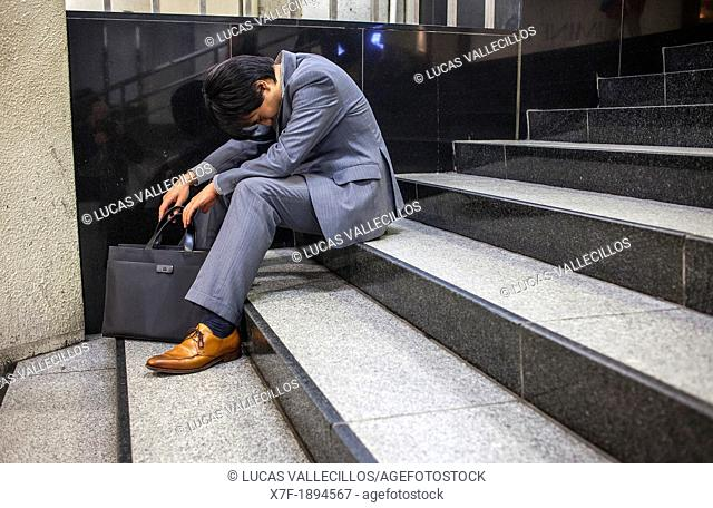 Salaryman sleeping after drink too much alcoholic beverages in Shinjuku station Subway Tokyo city, Japan, Asia