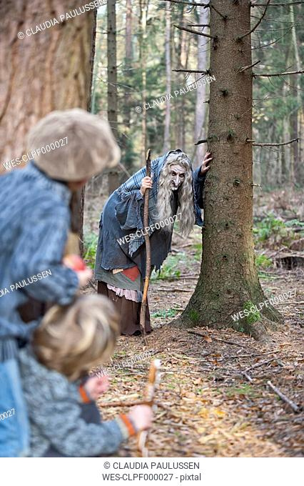 Germany, North Rhine-Westphalia, Moenchengladbach, Scene from fairy tale Hansel and Gretel, witch looking at children in the woods