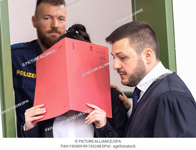 09 April 2019, Bavaria, München: When entering the courtroom, the defendant holds a red file cover in front of her face. The woman is accused of war crimes and...