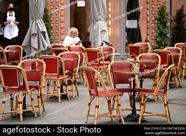 10 September 2021, Hessen, Frankfurt/Main: There are many free tables in front of a café in Frankfurt's new old town. The approval of the so-called 2G model...
