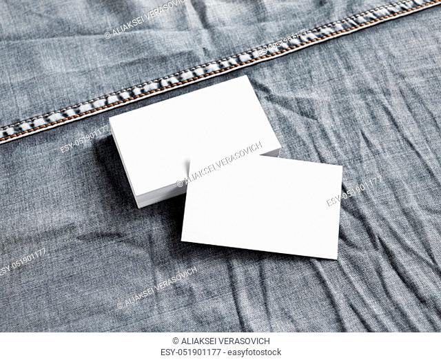 Blank white paper business cards on gray denim background