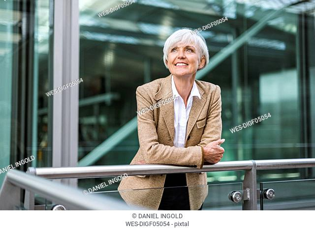 Portrait of smiling senior businesswoman leaning on railing in the city looking up