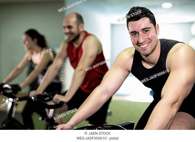 Group of young people training on exercise bike in gym