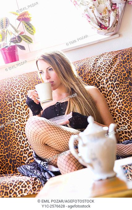 Drinking tea young woman on sofa
