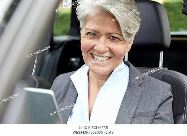 Portrait of smiling businesswoman with tablet sitting in a car