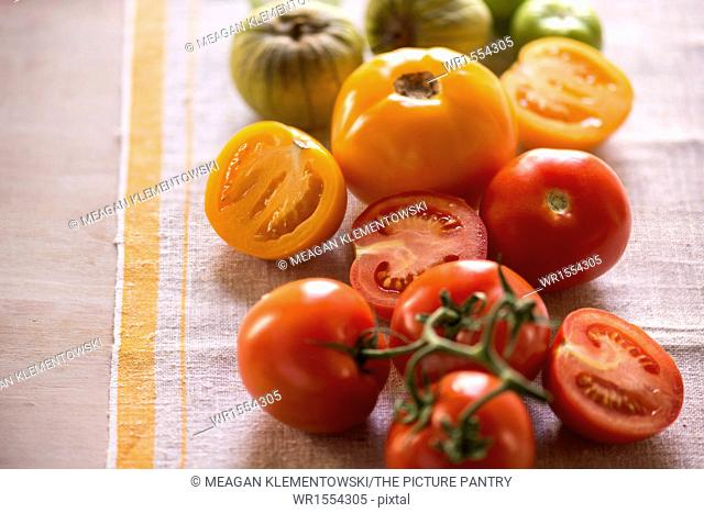 Variety of tomatoes, whole and cut, on rustic linen. Bright, summery feel