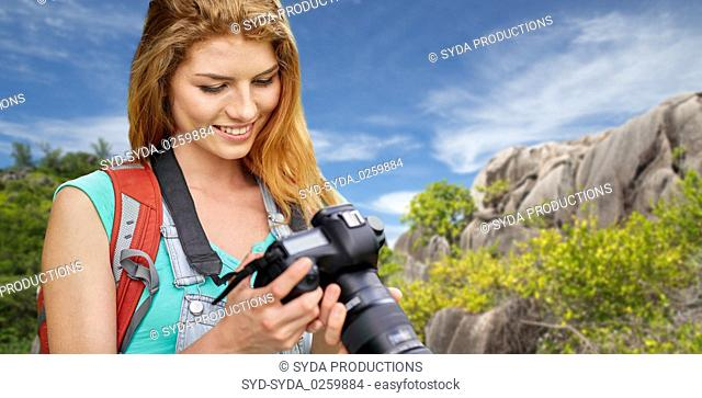 woman with backpack and camera over seychelles
