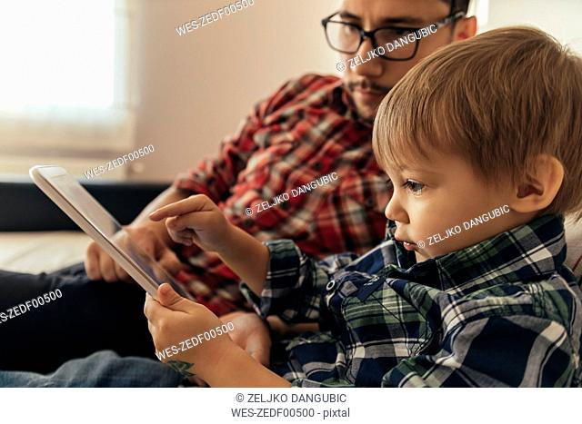 Father and son on couch using tablet