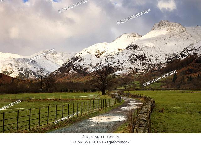 England, Cumbria, Langdale. Puddles of water on a farm track leading towards the snow covered Langdale Pikes