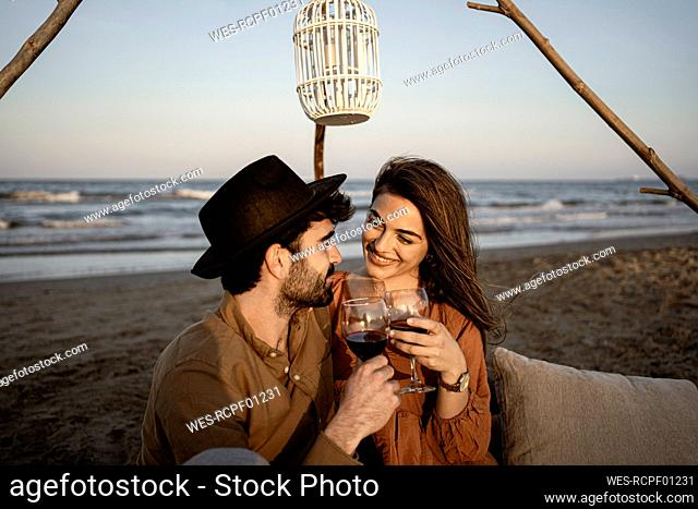 Smiling couple holding drinks while sitting at beach