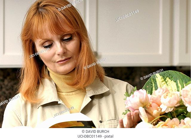 Woman reading book about roses