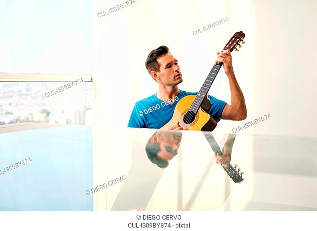 Guitarist playing guitar, view of skyscrapers in background