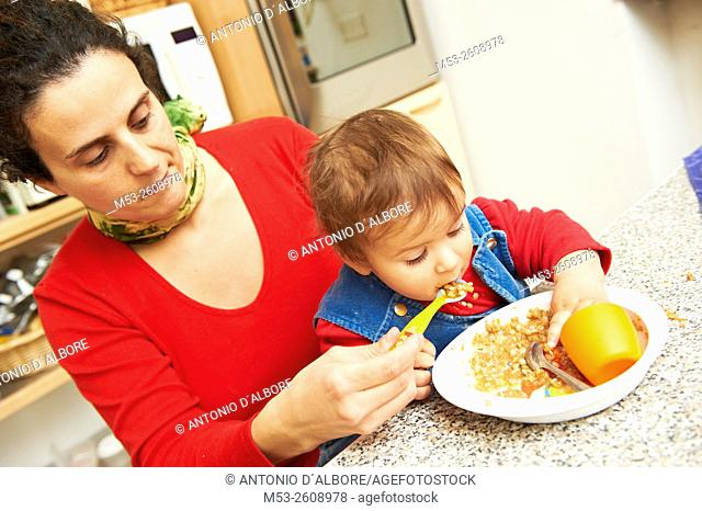 A caucasian mother feeding her eight months old baby girl