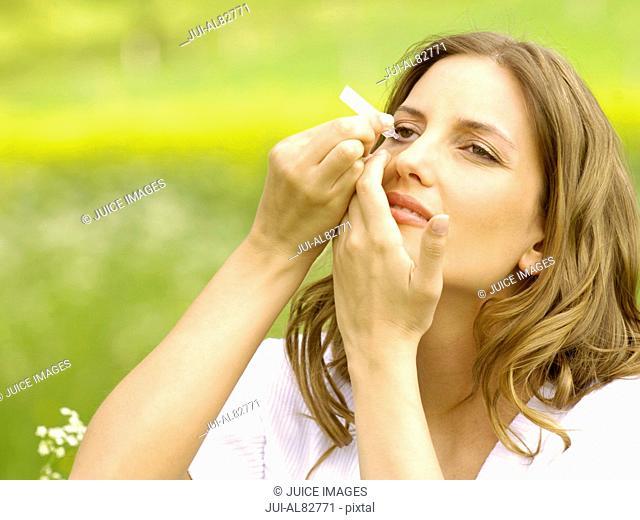 Woman using eye drops outdoors