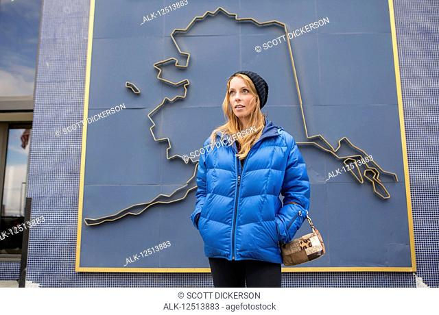 Mid adult woman standing in front of a 3D graphic of the outline of Alaska on a building in downtown Anchorage, South-central Alaska; Anchorage, Alaska