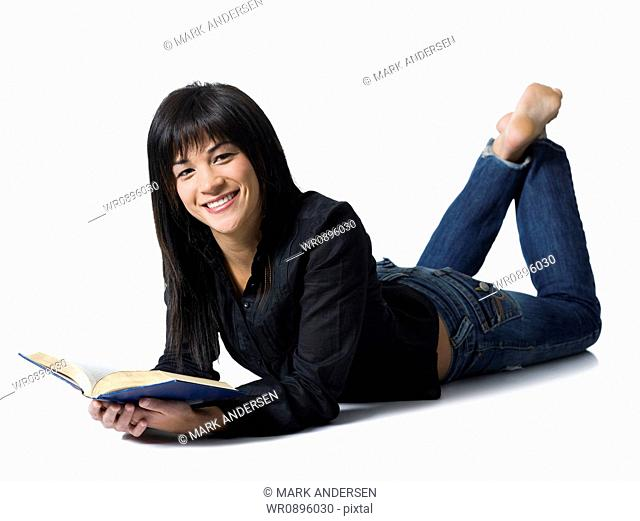 Woman lying down with hardcover book smiling