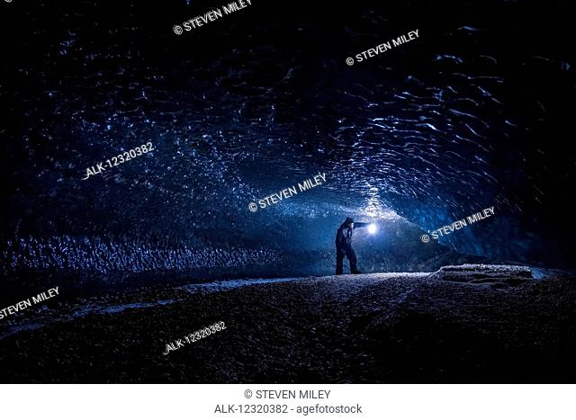 A man explores a dark tunnel beneath the ice of Canwell Glacier in the Alaska Range