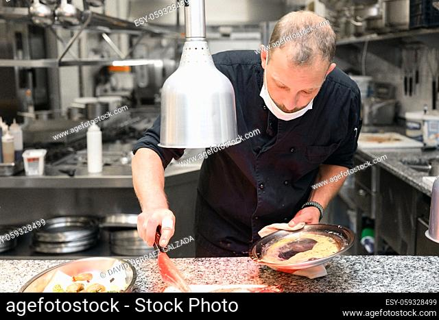 Chef in uniform cooking in a commercial kitchen. Male cook standing by kitchen counter preparing food. High quality photo
