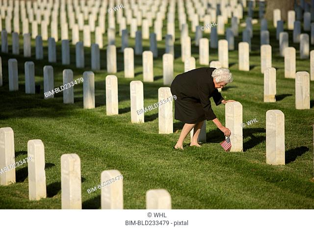 Caucasian widow placing American flag at cemetery gravestone