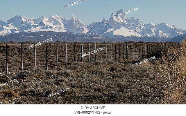Pan across a fenced region in the far Southern region of Patagonia with the Fitzroy Range in background