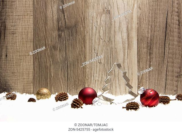 christmas decoration with wooden background, snow, christmas baubles red, gold and pine cones