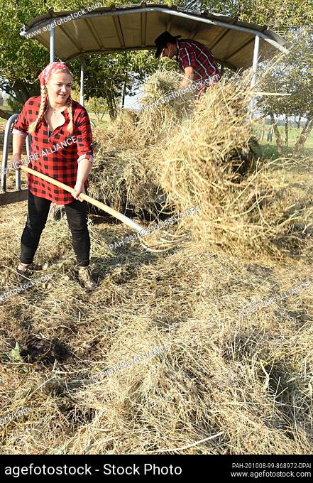 01 October 2020, Saxony, Wermsdorf: Cora Lechner works in her bison enclosure with her life partner Johannes Boos at a storage place for organic hay