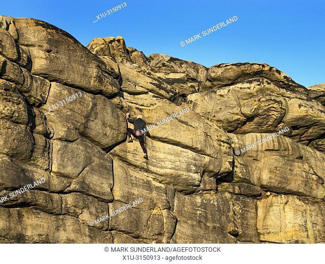 Rock climber at Almscliff Crag millstone grit outcrop near Harrogate North Yorkshire England