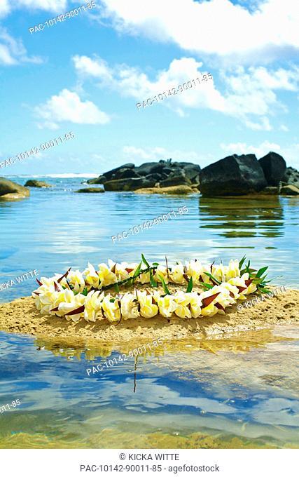 Hawaii, Kauai, Anahola, Shark's Hei'au along ocean, Plumeria lei on sand