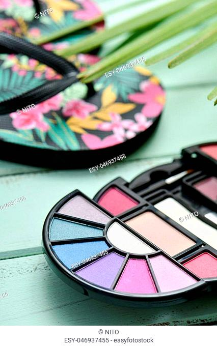 closeup of an eye shadow palette, a pair of colorful flower-patterned flip-flops and a palm leaf, on a pale blue rustic wooden surface