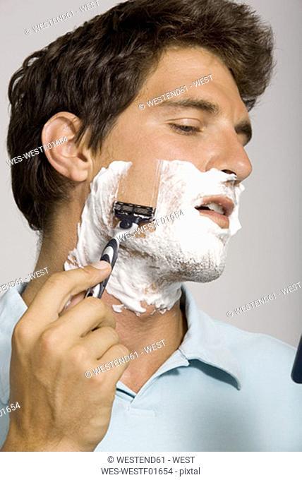 Young man shaving, portrait