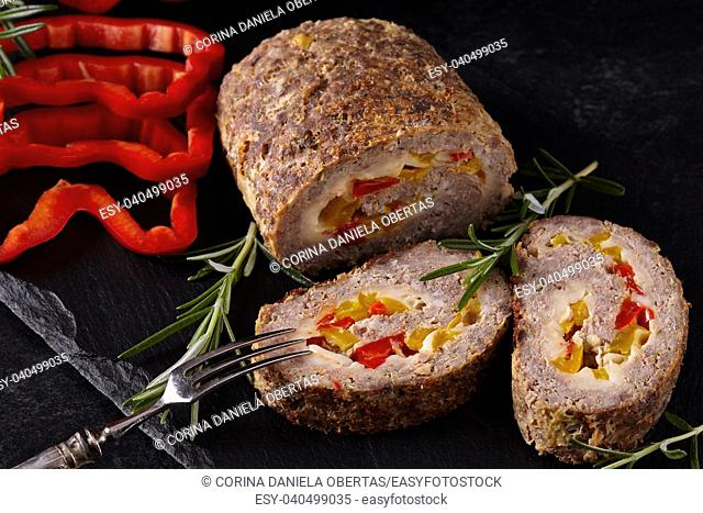 Closeup of minced meat loaf with red and yellow pepper and cheese