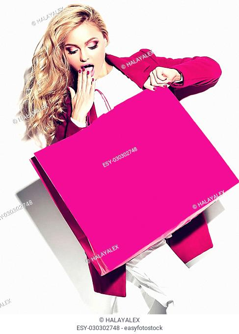portrait of beautiful cute happy sweet surprised blonde woman girl holding in her hands big shopping bag in hipster pink clothes isolated on white