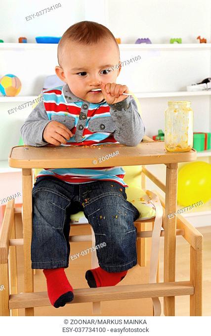 Baby beim essen von Babybrei aus dem Glas