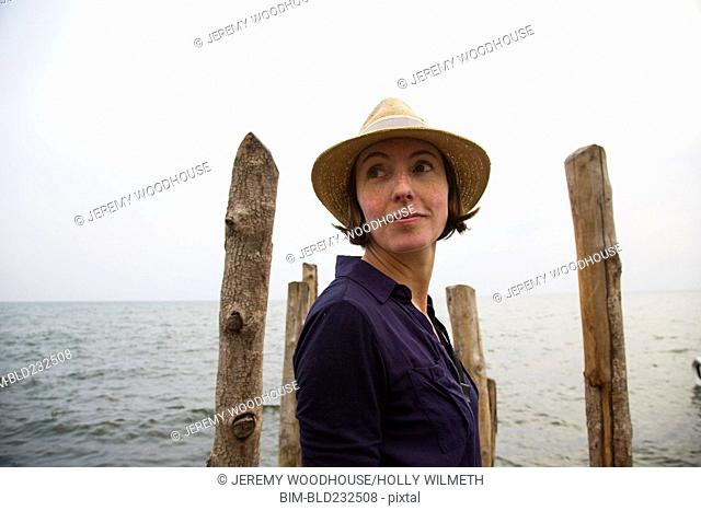Woman standing on dock at lake looking over shoulder