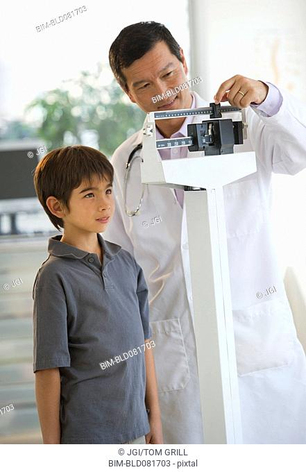 Doctor weighing boy on scale