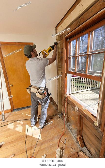 Hispanic carpenter using reciprocating saw to remove window and cut access doorway