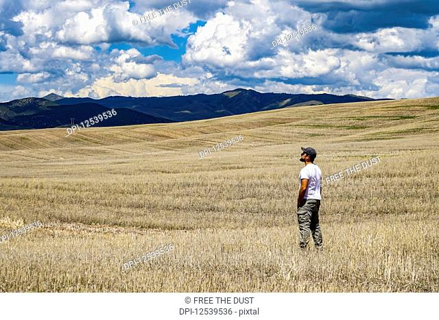 Standing in a vast farm field looking towards the mountains; Utah, United States of America
