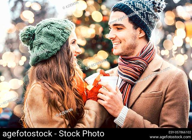Woman and man drinking mulled wine on Christmas Market in front of tree
