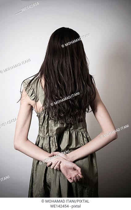 Rear view of a sad slender woman standing with hands behind her back