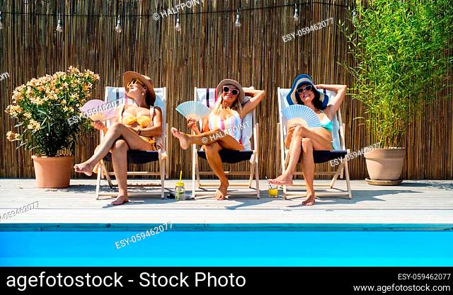 Group of cheerful women seniors sitting by swimming pool outdoors in backyard, relaxing with fan